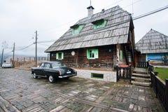 Παλαιό αυτοκίνητο που σταθμεύουν κοντά στο ξύλινο σπίτι Στοκ εικόνες με δικαίωμα ελεύθερης χρήσης