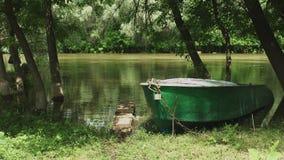 Παλαιό αλιευτικό σκάφος στην ακτή του ήρεμου ποταμού απόθεμα βίντεο