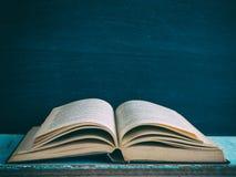 Παλαιό βιβλίο ανοικτό σε έναν ξύλινο πίνακα Στοκ Εικόνες