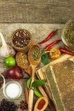 Παλαιό βιβλίο των συνταγών μαγειρικής Μαγειρικό βιβλίο υποβάθρου και συνταγής με τα διάφορα καρυκεύματα στον ξύλινο πίνακα Στοκ Φωτογραφίες