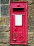 Παλαιό βρετανικό κόκκινο μετα κιβώτιο που τίθεται σε έναν τοίχο πετρών με την κλειδαρότρυπα Στοκ Φωτογραφίες