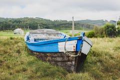 Παλαιό εγκαταλειμμένο ξύλινο αλιευτικό σκάφος που προσαράσσουν στο έδαφος και τη χλόη Στοκ φωτογραφίες με δικαίωμα ελεύθερης χρήσης