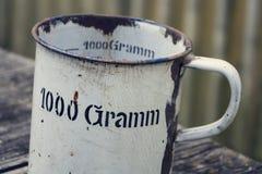 Παλαιό εκλεκτής ποιότητας μεταλλικό φλυτζάνι για τις στάσεις 1000 γραμμαρίων στο ξύλινο υπόβαθρο Στοκ εικόνα με δικαίωμα ελεύθερης χρήσης
