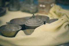 Παλαιό ελληνικό επιτραπέζιο σκεύος μετάλλων που καλύπτεται με ένα κίτρινο μάλλινο ύφασμα Ελληνικό επιτραπέζιο σκεύος και παράδοση Στοκ Φωτογραφίες
