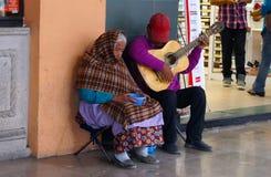 Παλαιό ζεύγος με μια κιθάρα που περιμένει τα χρήματα Στοκ εικόνες με δικαίωμα ελεύθερης χρήσης