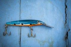 Παλαιό θέλγητρο αλιείας στο μπλε ξύλινο υπόβαθρο Στοκ εικόνα με δικαίωμα ελεύθερης χρήσης