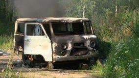 Παλαιό καίγοντας αυτοκίνητο που εκπέμπει τον καπνό σε έναν κενό θερινό τομέα φιλμ μικρού μήκους