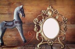 Παλαιό κενό βικτοριανό πλαίσιο ύφους και παλαιό άλογο λικνίσματος πέρα από τον ξύλινο πίνακα Στοκ εικόνες με δικαίωμα ελεύθερης χρήσης