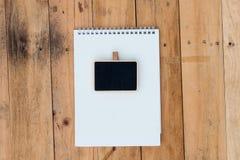 Παλαιό κενό ημερολόγιο και μαύρος πίνακας σε ξύλινο στοκ εικόνα με δικαίωμα ελεύθερης χρήσης