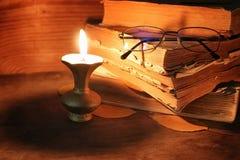 Παλαιό κουρελιασμένο βιβλίο σε ένα ξύλινο αναμμένο πίνακας κερί και τα γυαλιά Στοκ Φωτογραφίες