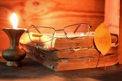 Παλαιό κουρελιασμένο βιβλίο σε ένα ξύλινο αναμμένο πίνακας κερί και τα γυαλιά Στοκ Εικόνα