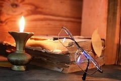 Παλαιό κουρελιασμένο βιβλίο σε ένα ξύλινο αναμμένο πίνακας κερί και τα γυαλιά Στοκ φωτογραφίες με δικαίωμα ελεύθερης χρήσης