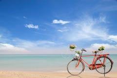 Παλαιό κόκκινο ποδήλατο με τα λουλούδια καλαθιών στην όμορφη παραλία τροπική Στοκ Φωτογραφίες