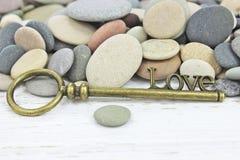Παλαιό κλειδί για την αγάπη σε ένα υπόβαθρο πετρών παραλιών Στοκ Φωτογραφία