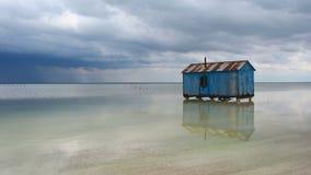 Παλαιό μπλε σπίτι που εγκαταλείπεται στη μέση της αλατισμένης λίμνης κατά τη διάρκεια μιας θύελλας προσέγγισης Salar Baskunchak απόθεμα βίντεο