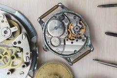 Παλαιό να βρεθεί ρολογιών που αποσυντίθεται στον πίνακα με τα εργαλεία επισκευής Στοκ Εικόνα