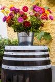 Παλαιό ξύλινο βαρέλι και όμορφα ζωηρόχρωμα λουλούδια Στοκ Φωτογραφία