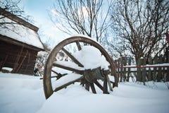Παλαιό ξύλινο εξοχικό σπίτι και ξύλινη ρουμανική ρόδα που καλύπτονται από το χιόνι Κρύα χειμερινή ημέρα στην επαρχία Παραδοσιακά  Στοκ Εικόνα