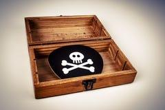 Παλαιό ξύλινο κιβώτιο με το σύμβολο πειρατών - κρανίο και κόκκαλα στο Μαύρο Στοκ Εικόνα