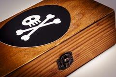Παλαιό ξύλινο κιβώτιο με το σύμβολο πειρατών - κρανίο και κόκκαλα στο Μαύρο Στοκ Εικόνες