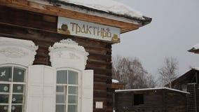 Παλαιό ξύλινο σπίτι με τις φωτεινές στάσεις πινάκων σημαδιών στο χειμερινό χωριό απόθεμα βίντεο