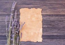 Παλαιό λουλούδι εγγράφου και lavender στο σκοτεινό ξύλινο επιτραπέζιο υπόβαθρο στοκ εικόνες με δικαίωμα ελεύθερης χρήσης