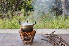 Παλαιό δοχείο αλουμινίου στη σόμπα με την πυρκαγιά και τον καπνό, λαϊκός μαγειρεύοντας τρόπος στοκ φωτογραφίες