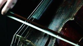 Παλαιό παιχνίδι βιολοντσέλων σε μια μαύρη κινηματογράφηση σε πρώτο πλάνο υποβάθρου φιλμ μικρού μήκους