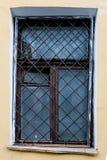 Παλαιό παράθυρο με ένα σκουριασμένο κιγκλίδωμα σε έναν παλαιό τοίχο με τα τούβλα Στοκ Φωτογραφία