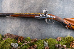Παλαιό παλαιό μακρύ πυροβόλο όπλο με τη δασική ακόμα ζωή στο γκρίζο υπόβαθρο, ιστορικά όπλα Στοκ Εικόνες