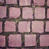 Παλαιό πεζοδρόμιο με τις ρόδινες χρωματισμένες πέτρες κλείστε επάνω Στοκ Φωτογραφία