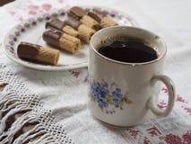 Παλαιό πελεκημένο φλυτζάνι με το μαύρο καφέ στο αγροτικό τραπεζομάντιλο με το plat στοκ εικόνα με δικαίωμα ελεύθερης χρήσης