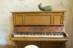 Παλαιό πιάνο και πράσινο κολοκύθι κολοκυθιών στο παλαιό δωμάτιο φέουδων Στοκ εικόνα με δικαίωμα ελεύθερης χρήσης