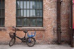 Παλαιό ποδήλατο και το παλαιό τούβλινο buiding υπόβαθρο Στοκ Εικόνες