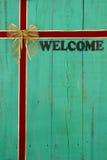 Παλαιό πράσινο ευπρόσδεκτο σημάδι με το κόκκινο και χρυσό υπόβαθρο Χριστουγέννων κορδελλών βελούδου Στοκ Φωτογραφίες