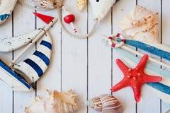 Παλαιό πρότυπο παιχνιδιών βαρκών πανιών με το σχοινί και θαλασσινό κοχύλι στο άσπρο ξύλινο υπόβαθρο - ναυτικό υπόβαθρο Στοκ εικόνα με δικαίωμα ελεύθερης χρήσης