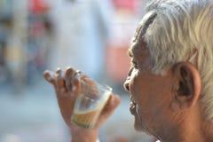 Παλαιό ρουφώντας γουλιά γουλιά τσάι ατόμων κάτω από τον ήλιο Στοκ Φωτογραφία
