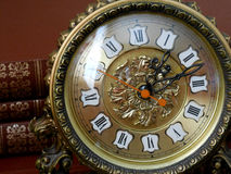 Παλαιό ρολόι σε ένα υπόβαθρο των βιβλίων Στοκ εικόνα με δικαίωμα ελεύθερης χρήσης
