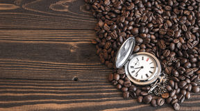 Παλαιό ρολόι τσεπών που βρίσκεται στα φασόλια καφέ Στοκ εικόνα με δικαίωμα ελεύθερης χρήσης