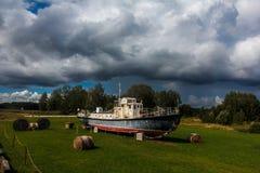 Παλαιό σκάφος στον τομέα σανού με τα μεγάλα άσπρα γκρίζα αυξομειούμενα σύννεφα Στοκ εικόνες με δικαίωμα ελεύθερης χρήσης