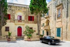 Παλαιό σπίτι πετρών με τα ζωηρόχρωμα παράθυρα και το μαύρο κλασικό μετατρέψιμο αυτοκίνητο ύφους - Mdina, Μάλτα Στοκ Εικόνα