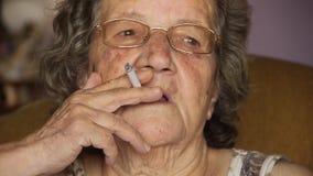 Παλαιό συνταξιούχο καπνίζοντας τσιγάρο γυναικών απόθεμα βίντεο
