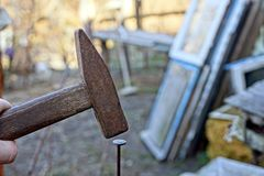 Παλαιό σφυρί που σφυρηλατεί ένα καρφί σε έναν ξύλινο πίνακα Στοκ φωτογραφίες με δικαίωμα ελεύθερης χρήσης