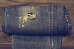 Παλαιό σχέδιο μόδας τζιν παντελόνι στο υπόβαθρο σύστασης δρύινου ξύλου, Σχισμένα τζιν ενός διαστήματος αντιγράφων μόδας Hipster σ Στοκ Εικόνες