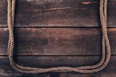 Παλαιό σχοινί στο ξύλινο υπόβαθρο σανίδων Στοκ Φωτογραφία