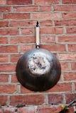 Παλαιό τηγάνι στο brickwall Στοκ Εικόνα