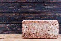 Παλαιό τούβλο στο ξύλινο γραφείο Στοκ φωτογραφίες με δικαίωμα ελεύθερης χρήσης