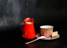 Παλαιό φλυτζάνι και πιατάκι και γάλα σε ένα πορτοκάλι και μια γκοφρέτα βάζων γυαλιού Στοκ Φωτογραφίες