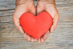 Παλαιό χέρι που κρατά την κόκκινη μορφή καρδιών Στοκ εικόνες με δικαίωμα ελεύθερης χρήσης