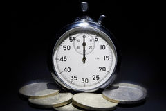 Παλαιό χρονόμετρο με διακόπτη σε ένα μαύρο υπόβαθρο με τα χρήματα Στοκ Εικόνες